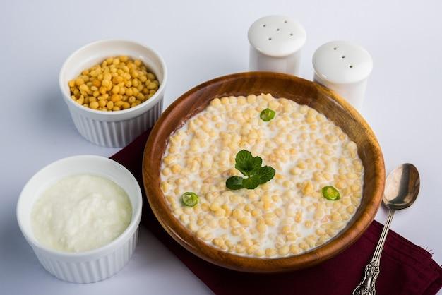 Dahi bundi ou boondi raita com requeijão, é um acompanhamento popular do rajastão, na índia. servido com coberturas de coentro em uma tigela sobre fundo colorido ou de madeira. foco seletivo