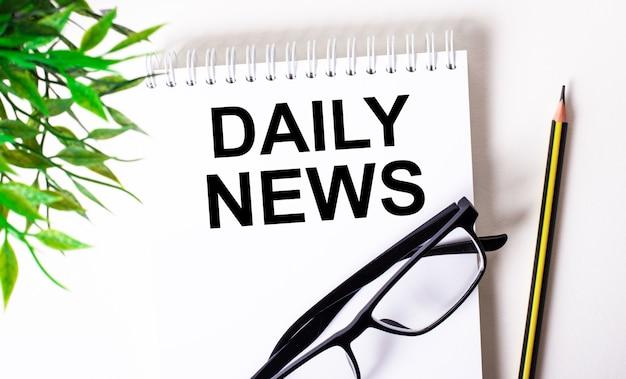 Daily news está escrito em um caderno branco ao lado de um lápis, óculos de armação preta e uma planta verde.