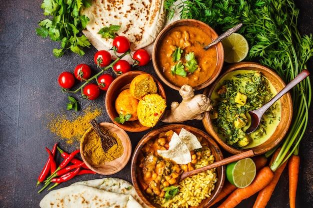 Dal, palak paneer, caril, arroz, chapati, chutney em bacias de madeira na mesa escura.