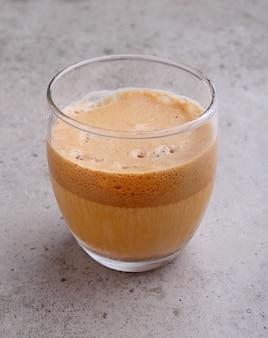 Dalgonð ° café em um copo sobre uma mesa de concreto