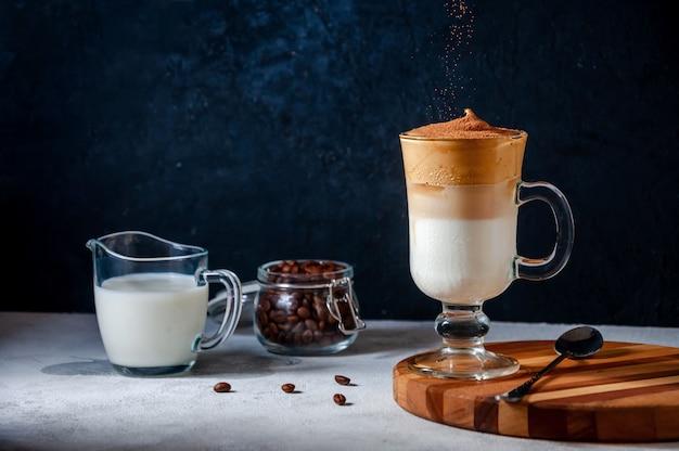 Dalgona café com peneirar cacau na parede escura. café chicoteado cremoso na moda. bebida fria de verão na coréia do sul