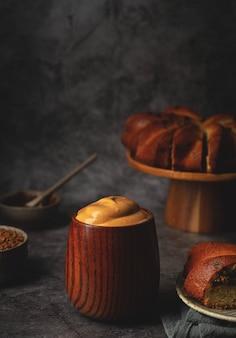 Dalgona café em um copo de madeira e um bolo em um carrinho. café batido fofo. bebida coreana de tendência.