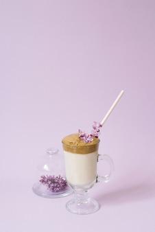 Dalgona café em um copo transparente com um tubo de papel, um prato com flores lilás em lilás