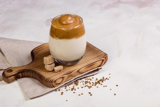 Dalgona café em um copo transparente na mesa.