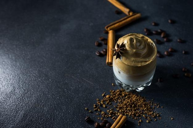 Dalgona café em um copo transparente sobre um fundo escuro. bebida sul-coreana com café instantâneo batido, açúcar e leite.