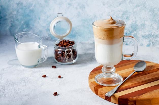 Dalgona café na superfície da luz. café chicoteado cremoso na moda. bebida fria de verão coreana