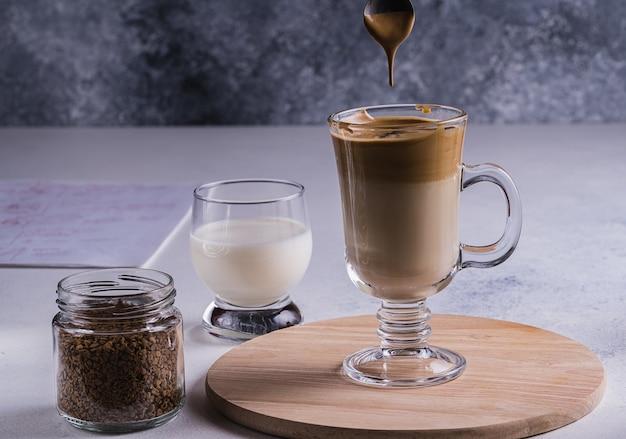 Dalgona espresso latte e ingredientes para sua preparação em uma mesa cinza. foco seletivo.