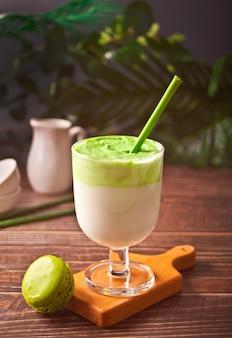 Dalgona matcha latte, chá verde matcha batido cremoso com planta no fundo.