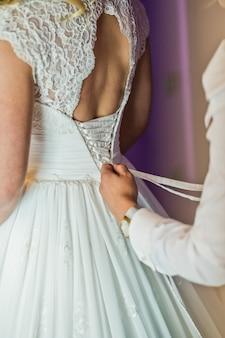 Dama de honra ajuda a vestir o vestido de casamento da noiva, interior do hotel, fundo roxo