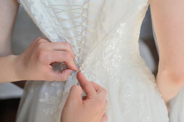 Dama de honra ajuda a vestir um vestido de noiva em uma manhã de casamento