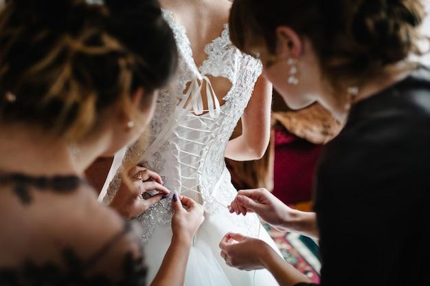 Dama de honra ajudando a noiva a apertar o espartilho e pegando seu vestido, preparando a noiva pela manhã para o dia do casamento.
