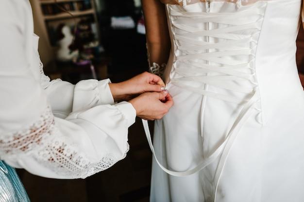 Dama de honra ajudando a noiva a apertar o espartilho e recebendo seu vestido, preparando a noiva pela manhã para o dia do casamento