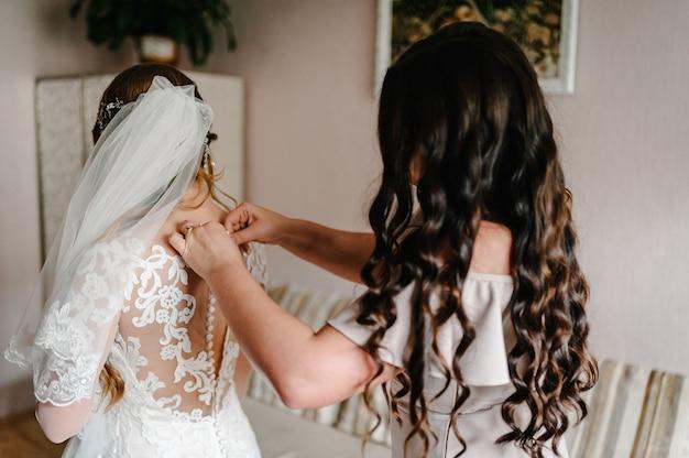 Dama de honra ajudando a noiva a fechar os botões do espartilho e a conseguir o vestido