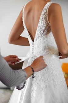 Dama de honra ajudando a noiva a vestir seu elegante vestido de noiva branco com um laço nas costas em um close-up nas mãos