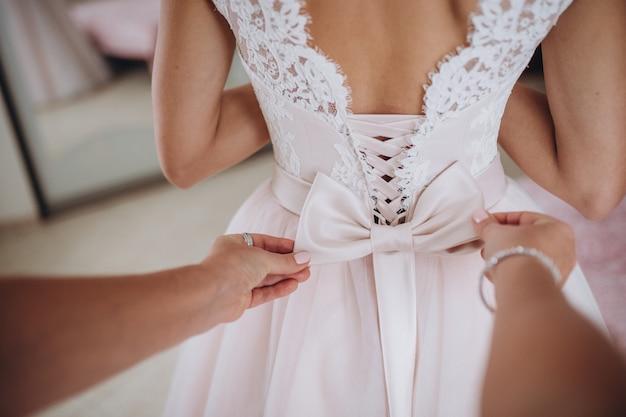 Dama de honra está ajudando a noiva a se vestir