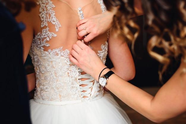 Dama de honra mãos aperta botões nas costas da noiva no vestido de casamento branco com espartilho