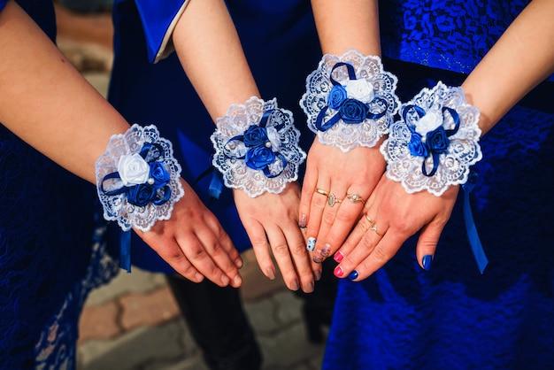 Dama de honra mãos closeup em vestidos azuis juntos