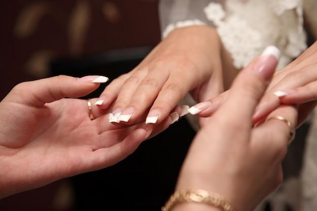 Dama de honra olha a manicure da noiva