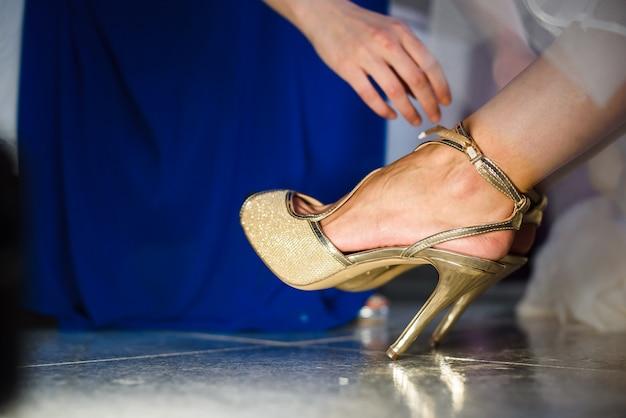 Dama de honra que ajuda a noiva nova a pôr sobre as sapatas antes da cerimônia de casamento.