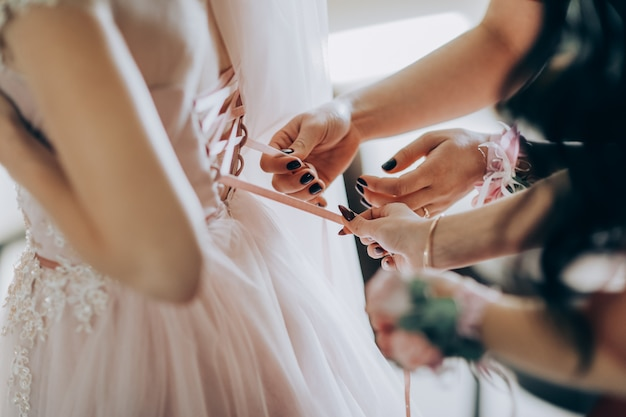 Dama de honra que prepara a noiva para o dia do casamento. a dama de honra ajuda a prender um vestido de noiva à noiva antes da cerimônia. melhor manhã de casamento