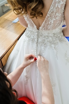 Damas de honra ajudar a noiva a usar um vestido de noiva