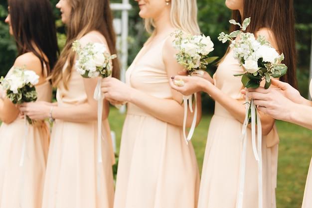 Damas de honra gloriosas em vestidos leves, segurando lindas flores