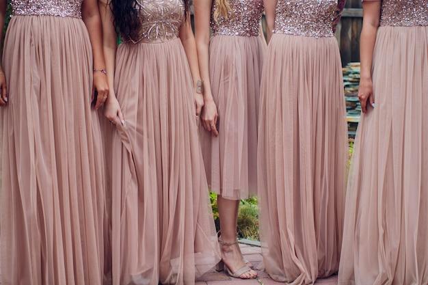 Damas de honra gloriosas em vestidos rosa