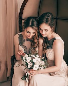 Damas de honra olhando para o buquê de casamento.