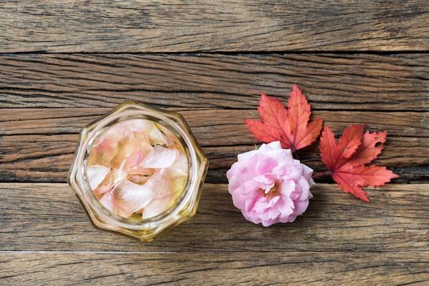 Damasco rosa e óleo de rosa em uma superfície de madeira velha.