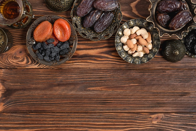 Damasco seco; passas pretas; datas e chá na tigela metálica na mesa de madeira