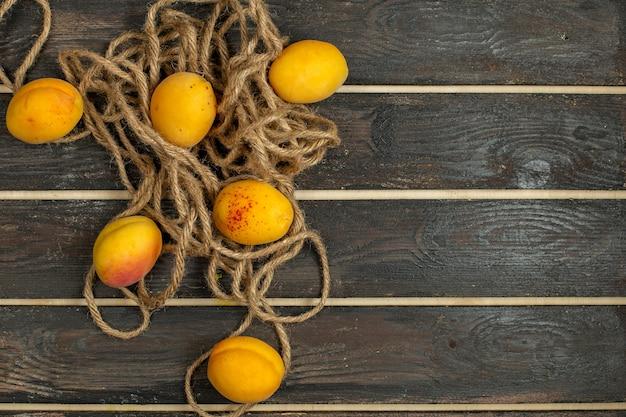 Damascos amarelos maduros e frutas frescas na mesa rústica