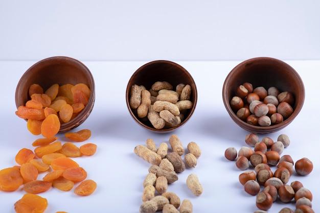 Damascos, amendoins e avelãs orgânicos secos em tigelas de madeira.