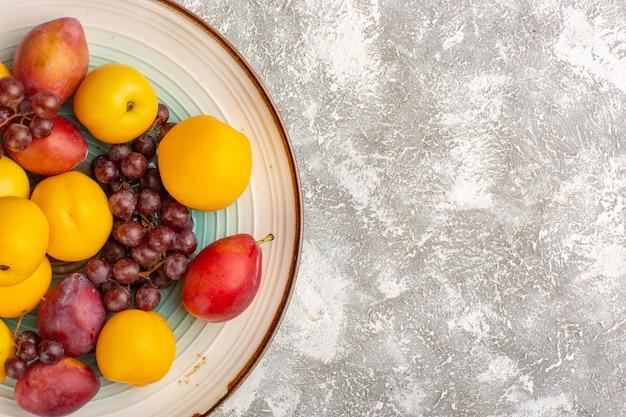 Damascos doces frescos com uvas vermelhas e ameixas no prato na superfície branca de cima