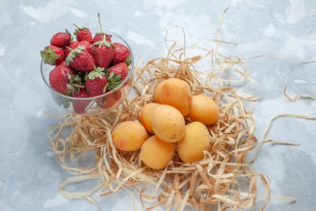 Damascos frescos e doces frutas maduras com morangos vermelhos no branco