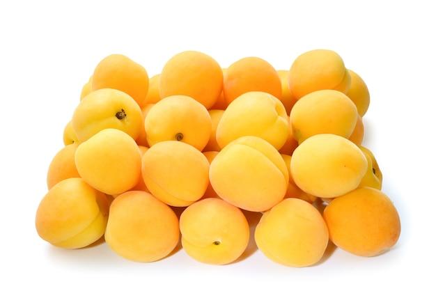 Damascos maduros e suculentos de laranja isolados na superfície branca