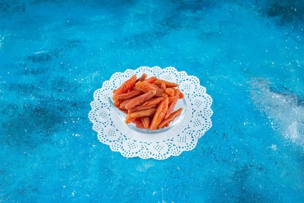 Damascos secos em uma tigela na montanha-russa, na mesa azul.