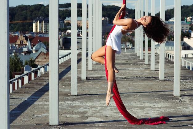 Dança aérea no telhado, dançarina de seda morena sexy em vestido branco