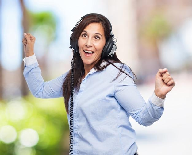 Dança da mulher com fones de ouvido