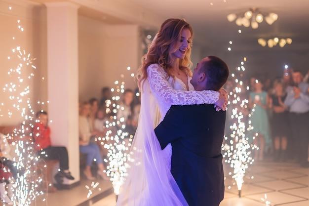 Dança de casamento no salão de um restaurante com fogos de artifício