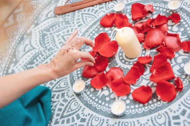 Dança de mãos femininas com mehendi sobre o altar de velas e pétalas de rosas, práticas de mulheres