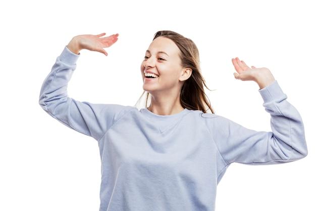 Dança de sorriso a moça em um casaco azul aprecia a vida. alegria e felicidade. isolado em um branco