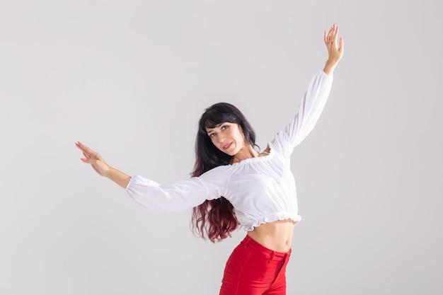 Dança latina, senhora bachata, jazz moderno e conceito de dança da moda - mulher jovem e bonita dançando na parede branca com espaço de cópia