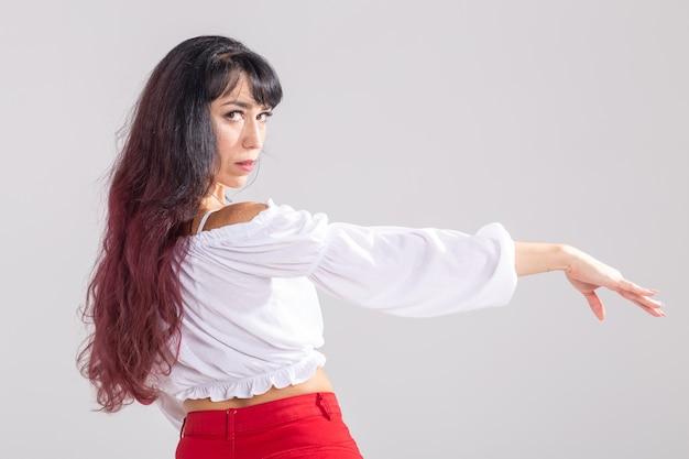 Dança latina, strip dance, conceito contemporâneo e bachata lady - mulher dançando improvisação e movendo seus longos cabelos sobre um fundo branco