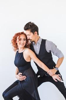 Dança social, bachata, kizomba, tango, salsa, conceito de gente. jovem casal dançando no branco