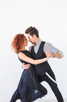 Dança social, bachata, kizomba, tango, salsa, conceito de pessoas - jovem casal dançando sobre branco