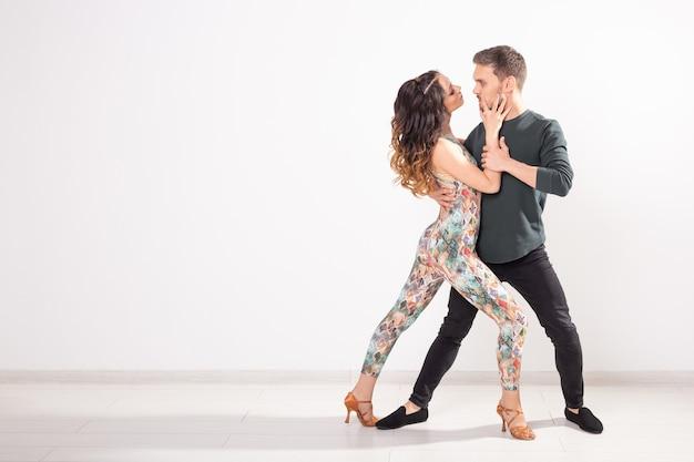Dança social, bachata, kizomba, tango, salsa, conceito de pessoas - jovem casal dançando sobre fundo branco com espaço de cópia