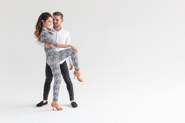 Dança social, bachata, kizomba, zouk, conceito de tango - homem abraça mulher enquanto dança sobre fundo branco com espaço de cópia