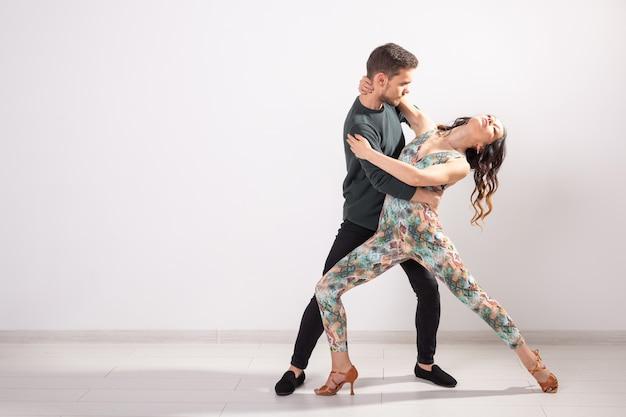 Dança social, bachata, salsa, kizomba, zouk, conceito de tango - homem abraça mulher enquanto dança sobre fundo branco com espaço de cópia