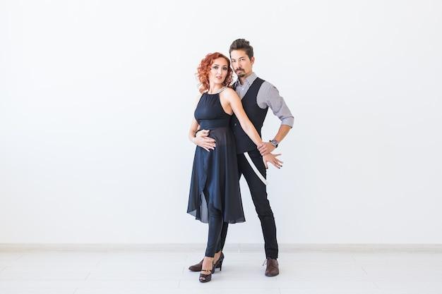 Dança social, kizomba, tango, salsa, conceito de gente - lindo casal dançando bachata no branco