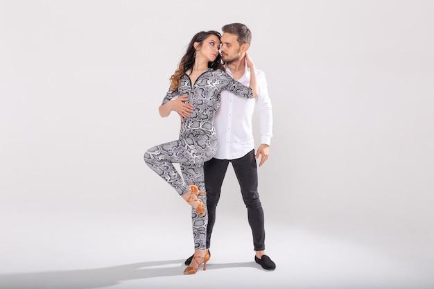 Dança social, kizomba, tango, salsa, conceito de pessoas - lindo casal dançando bachata no branco